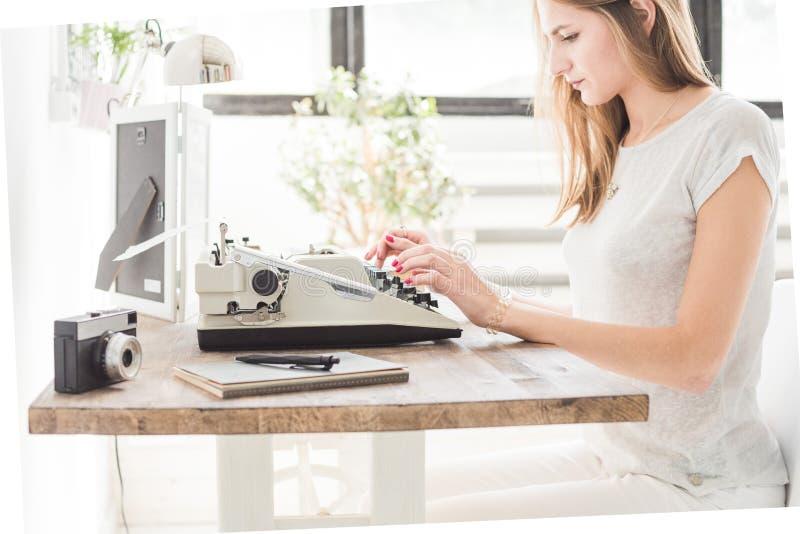 Mujer de negocios joven que trabaja en casa y que mecanografía en una máquina de escribir Espacio de trabajo escandinavo creativo imagen de archivo