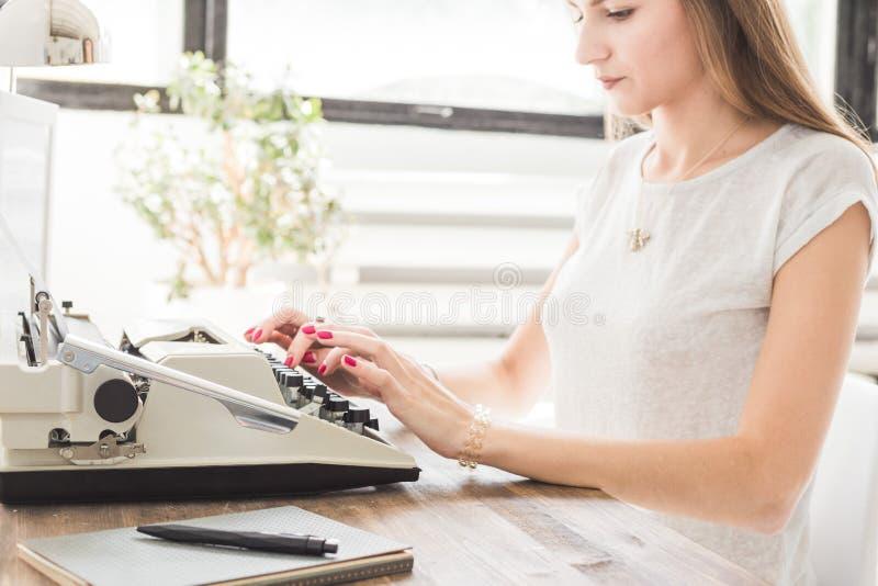 Mujer de negocios joven que trabaja en casa y que mecanografía en una máquina de escribir Espacio de trabajo escandinavo creativo fotos de archivo libres de regalías