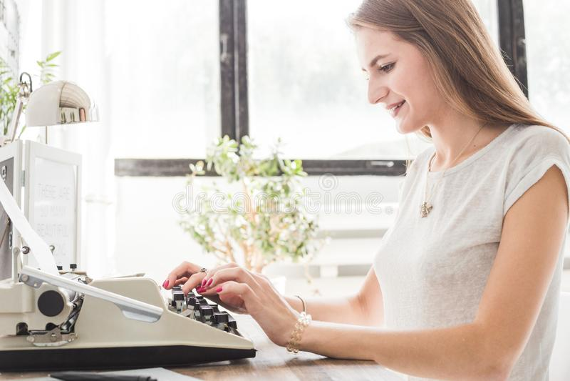 Mujer de negocios joven que trabaja en casa y que mecanografía en una máquina de escribir Espacio de trabajo escandinavo creativo foto de archivo