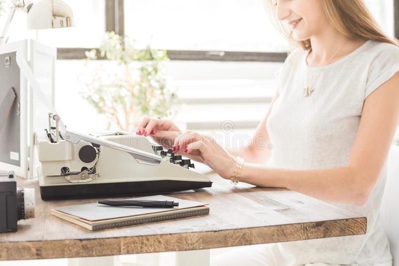 Mujer de negocios joven que trabaja en casa y que mecanografía en una máquina de escribir Espacio de trabajo escandinavo creativo fotos de archivo
