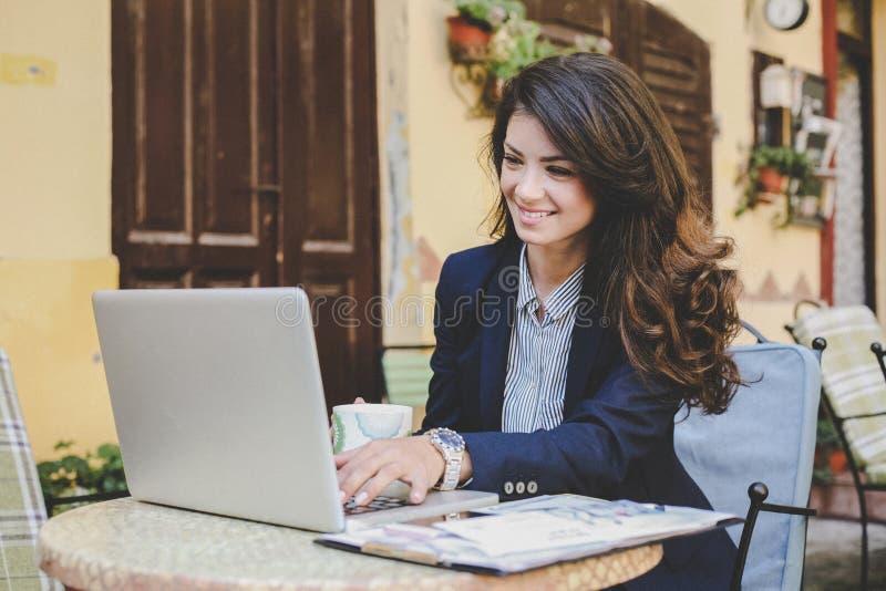 Mujer de negocios joven que trabaja en descanso para tomar café fotografía de archivo
