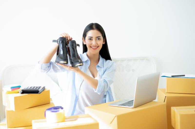 Mujer de negocios joven que trabaja los zapatos que se sostienen en línea de la pequeña empresa fotografía de archivo