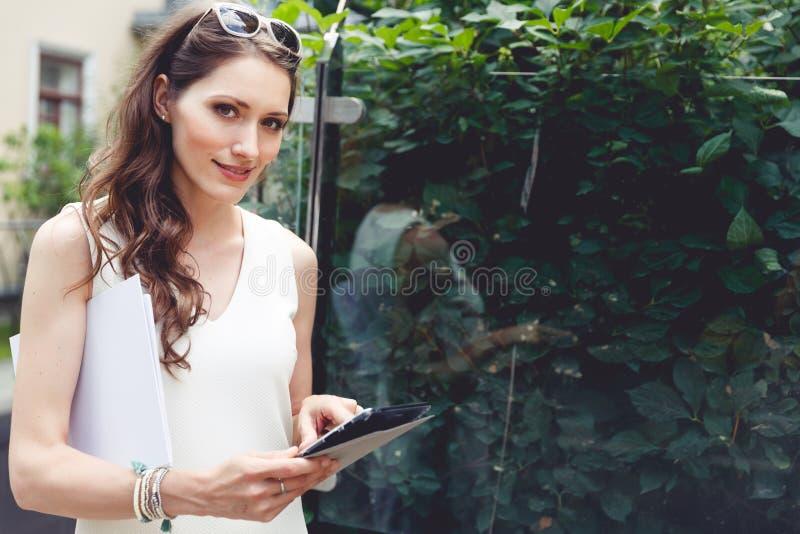 Mujer de negocios joven que usa la tableta digital y llevando a cabo documentos foto de archivo