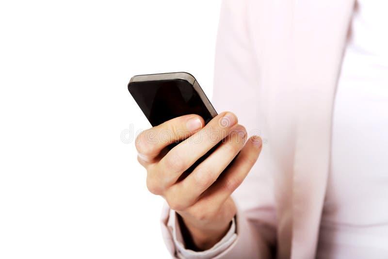 Mujer de negocios joven que usa un teléfono móvil imagen de archivo