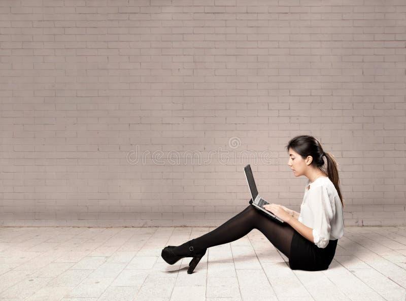 Mujer de negocios joven que usa una computadora portátil foto de archivo