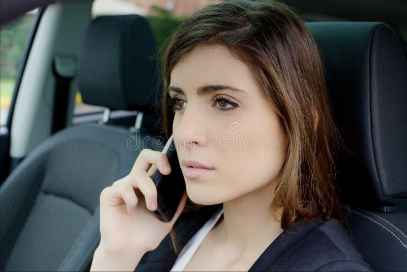 Mujer de negocios joven seria en el teléfono en coche imagenes de archivo
