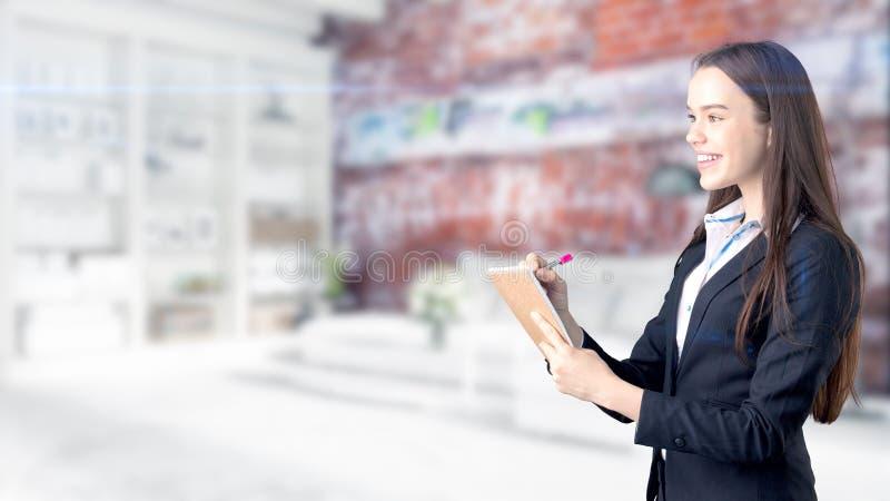 Mujer de negocios joven sobre fondo interior foto de archivo libre de regalías