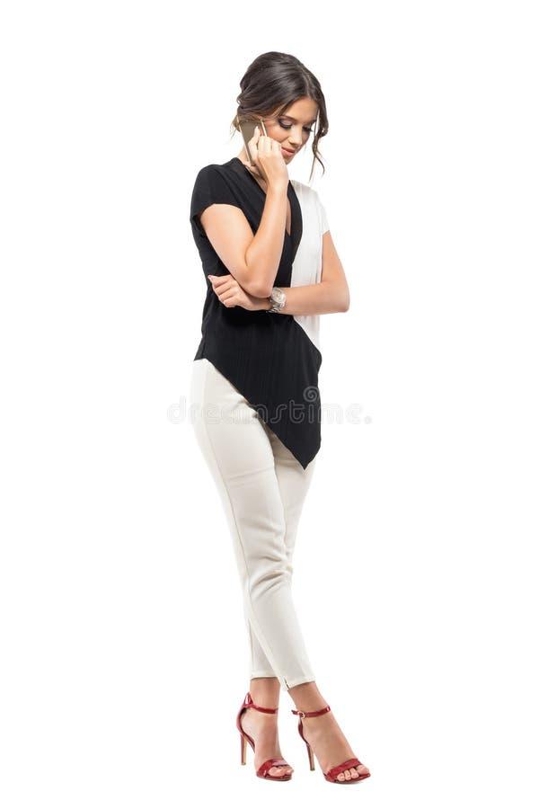 Mujer de negocios joven sonriente en traje que habla en el teléfono que mira abajo fotografía de archivo libre de regalías