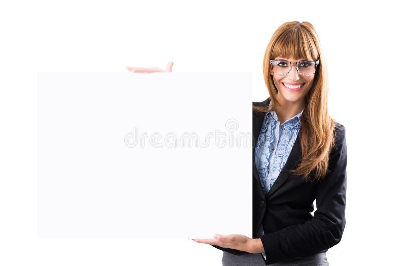 Mujer de negocios joven sonriente feliz que muestra el letrero en blanco foto de archivo