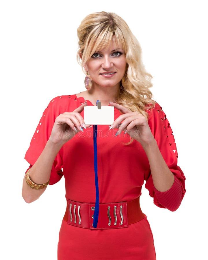 Mujer de negocios joven sonriente feliz que muestra la insignia en blanco foto de archivo