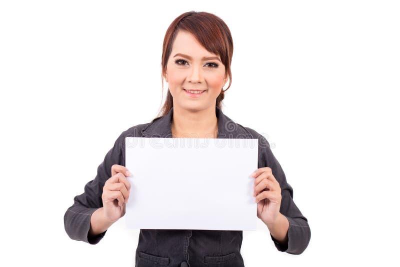 Mujer de negocios joven sonriente feliz que sostiene el letrero en blanco, imagen de archivo libre de regalías