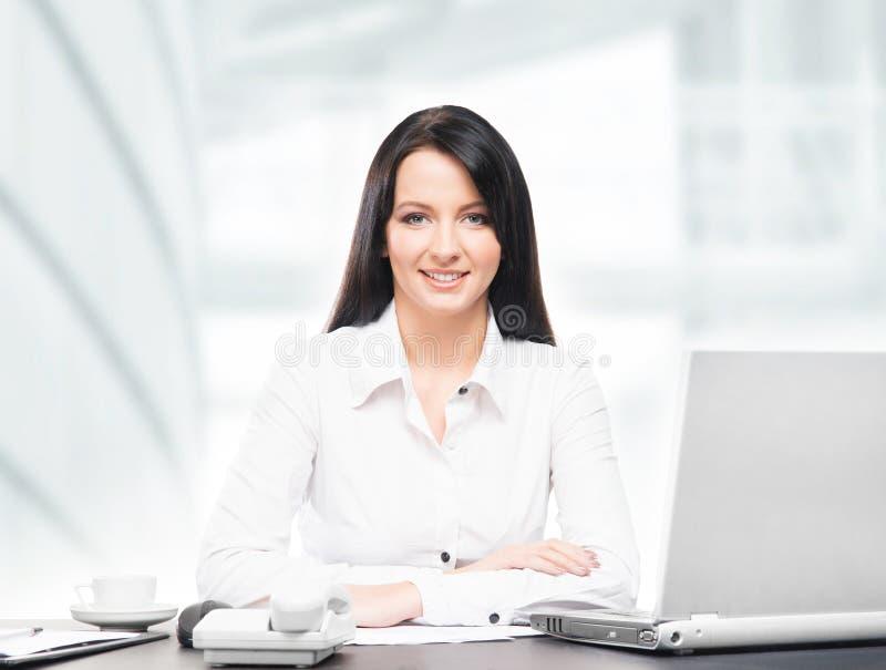 Mujer de negocios joven y atractiva que trabaja en oficina fotos de archivo