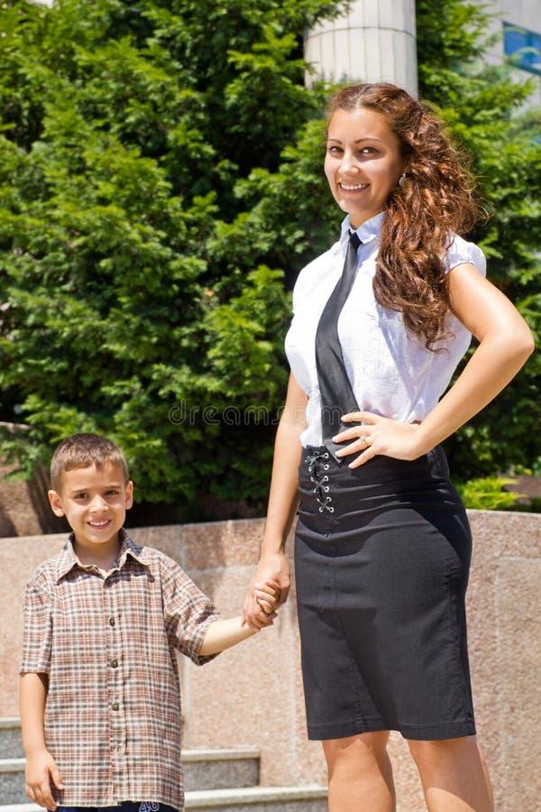 Mujer de negocios joven y su hijo que llevan a cabo las manos imagen de archivo