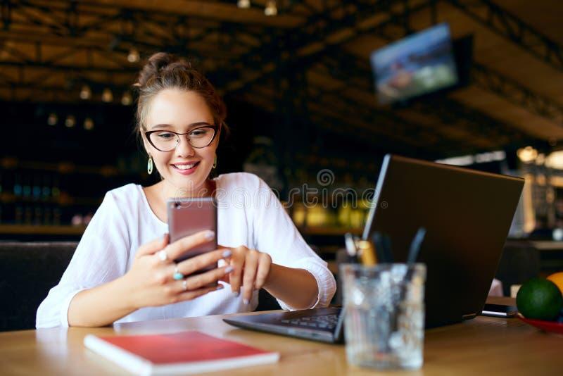 Mujer de negocios de la raza mixta que mecanografía un texto en smartphone Hembra asiática que sostiene un teléfono móvil moderno imagen de archivo