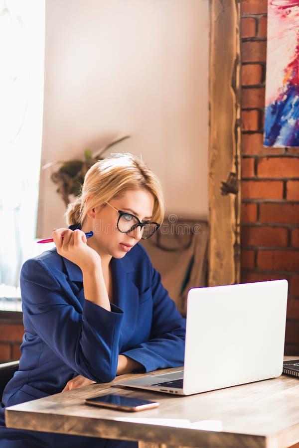 Mujer de negocios lista hermosa que se sienta en la tabla en el puesto de trabajo con el ordenador portátil imágenes de archivo libres de regalías