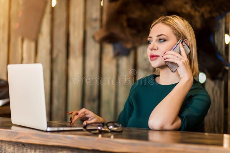Mujer de negocios lista hermosa que se sienta en la tabla en el puesto de trabajo con el ordenador port?til imagenes de archivo