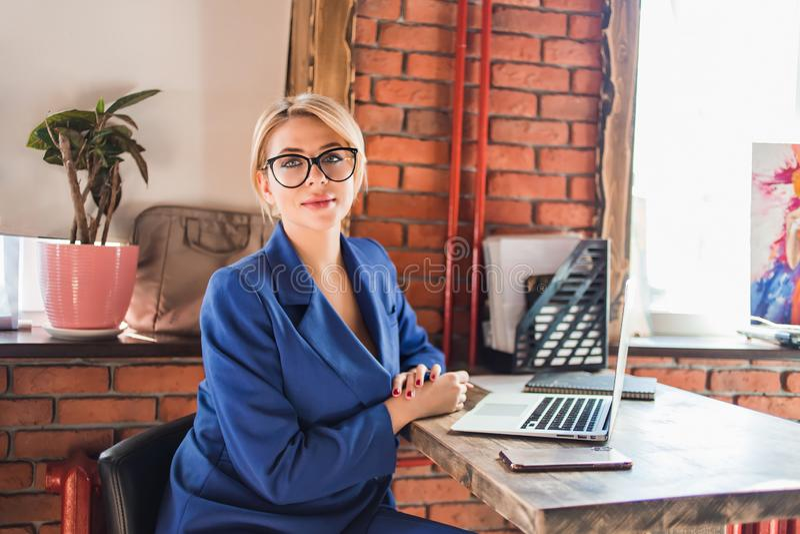 Mujer de negocios lista hermosa que se sienta en la tabla en el puesto de trabajo con el ordenador portátil imagen de archivo