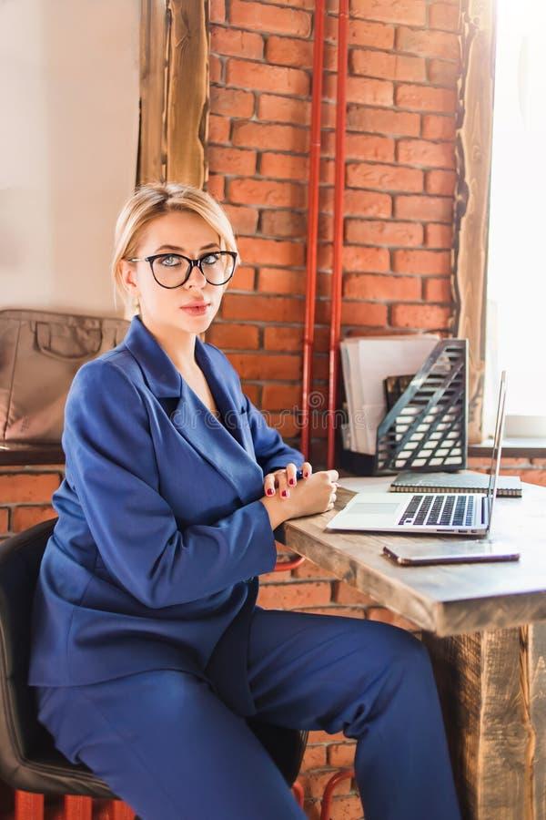 Mujer de negocios lista hermosa que se sienta en la tabla en el puesto de trabajo con el ordenador portátil fotografía de archivo