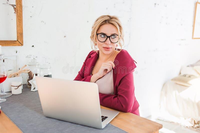 Mujer de negocios lista hermosa que se sienta en la tabla en el puesto de trabajo con el ordenador port?til imágenes de archivo libres de regalías