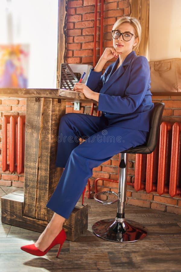 Mujer de negocios lista hermosa que se sienta en la tabla en el puesto de trabajo con el ordenador port?til imagen de archivo libre de regalías