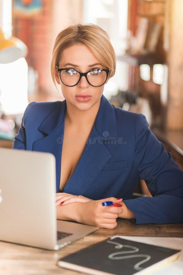 Mujer de negocios lista hermosa que se sienta en la tabla en el puesto de trabajo con el ordenador port?til fotos de archivo