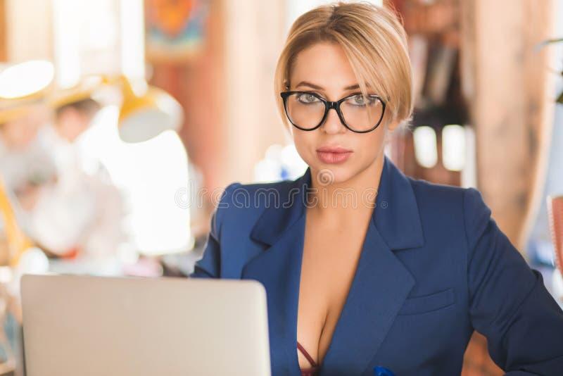 Mujer de negocios lista hermosa que se sienta en la tabla en el puesto de trabajo con el ordenador port?til fotos de archivo libres de regalías