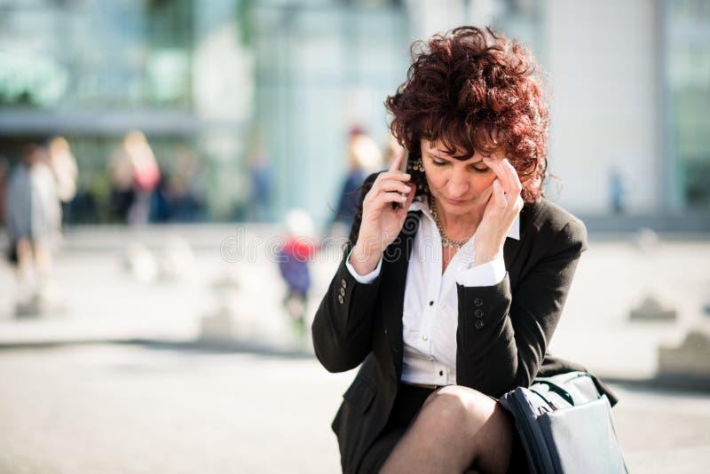 Mujer de negocios maduros con el teléfono en calle foto de archivo