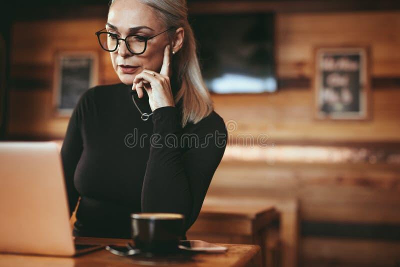 Mujer de negocios maduros en el café usando el ordenador portátil foto de archivo libre de regalías