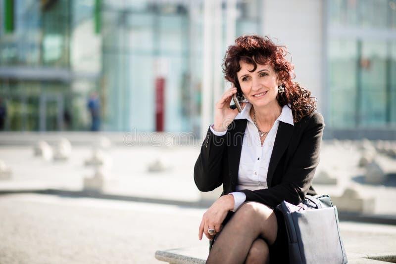 Mujer de negocios maduros en el teléfono en calle imagen de archivo libre de regalías
