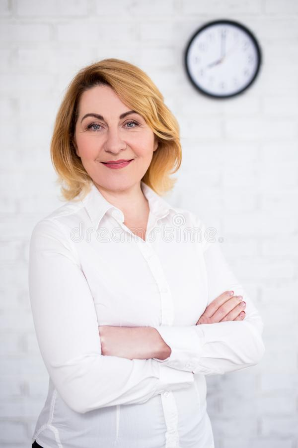 Mujer de negocios maduros que presenta sobre la pared blanca con el reloj de la oficina imágenes de archivo libres de regalías