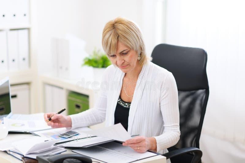 Mujer de negocios maduros que trabaja en la oficina foto de archivo