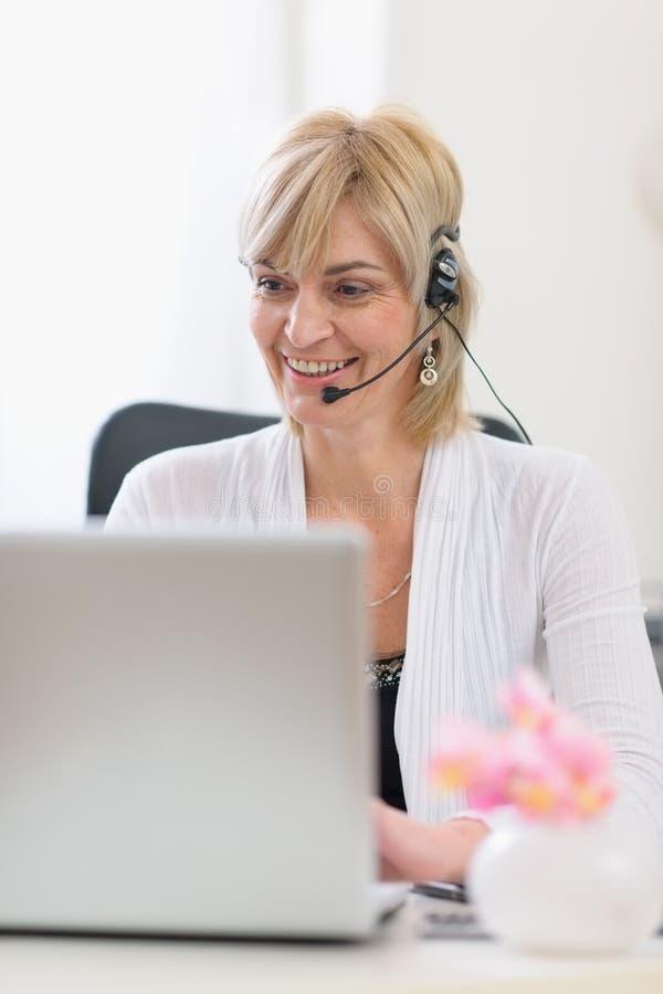 Mujer de negocios mayor con el receptor de cabeza usando la computadora portátil imagen de archivo