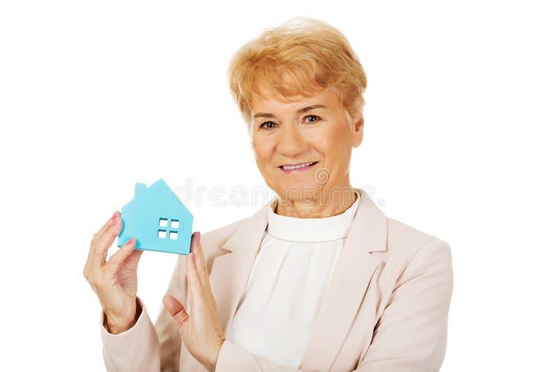 Mujer de negocios mayor de la sonrisa que sostiene la casa del papel azul foto de archivo libre de regalías