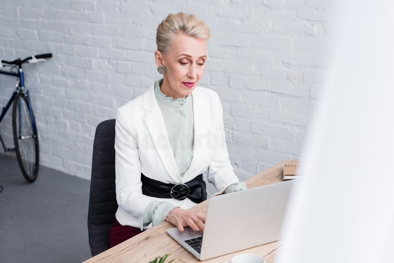 mujer de negocios mayor elegante que trabaja con el ordenador portátil imagen de archivo