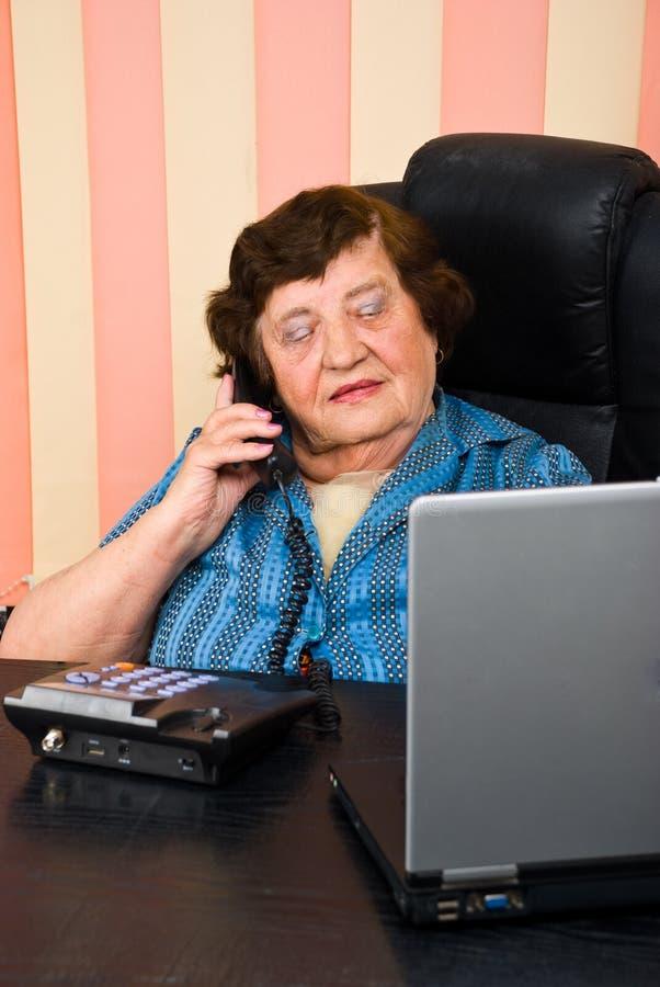 Mujer de negocios mayor ocupada en oficina fotos de archivo