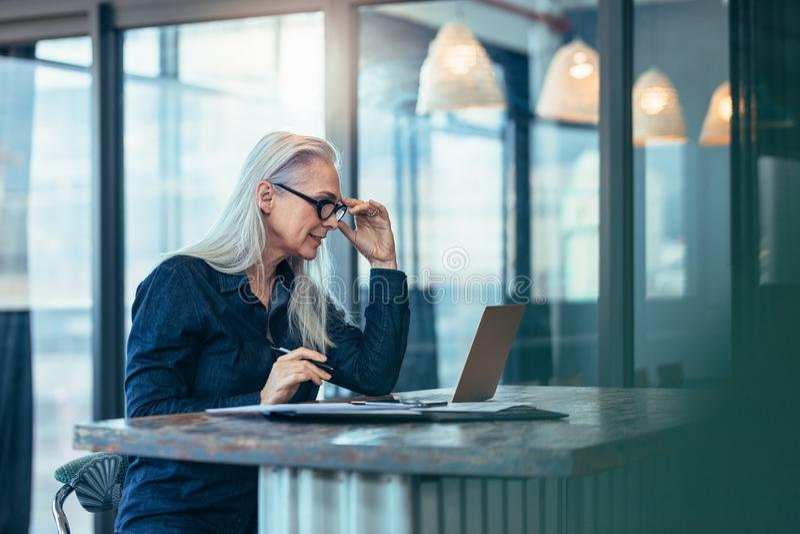 Mujer de negocios mayor que trabaja en el ordenador portátil en oficina fotos de archivo
