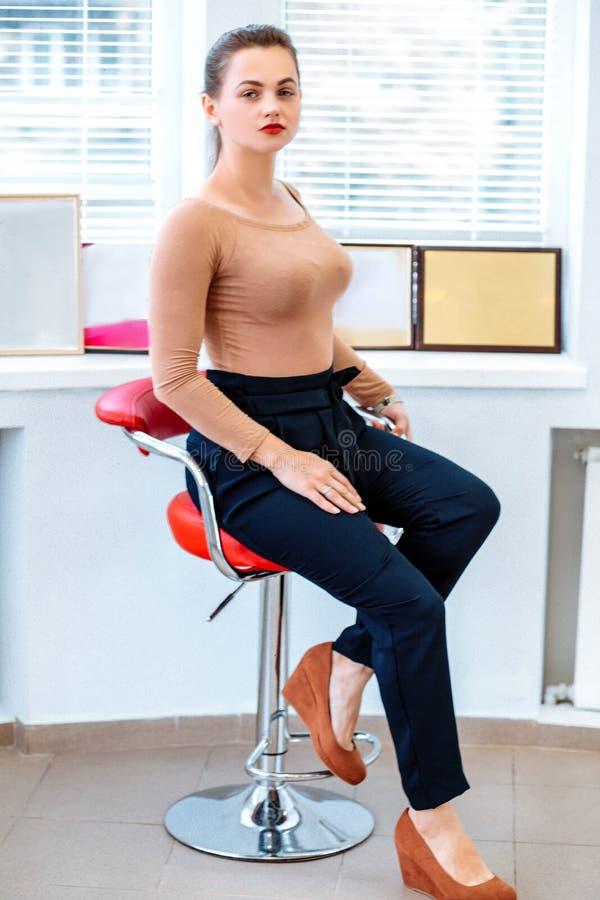Mujer de negocios moderna acertada en la silla imagen de archivo