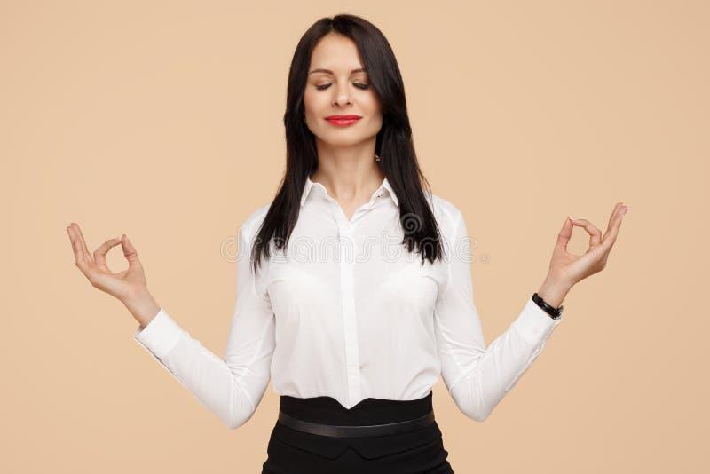 Mujer de negocios moderna joven feliz que medita sobre fondo beige Meditación, religión y prácticas espirituales imagenes de archivo