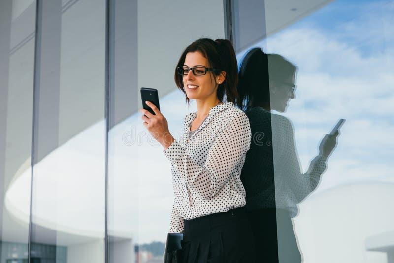 Mujer de negocios moderna que manda un SMS en el teléfono móvil fotografía de archivo libre de regalías