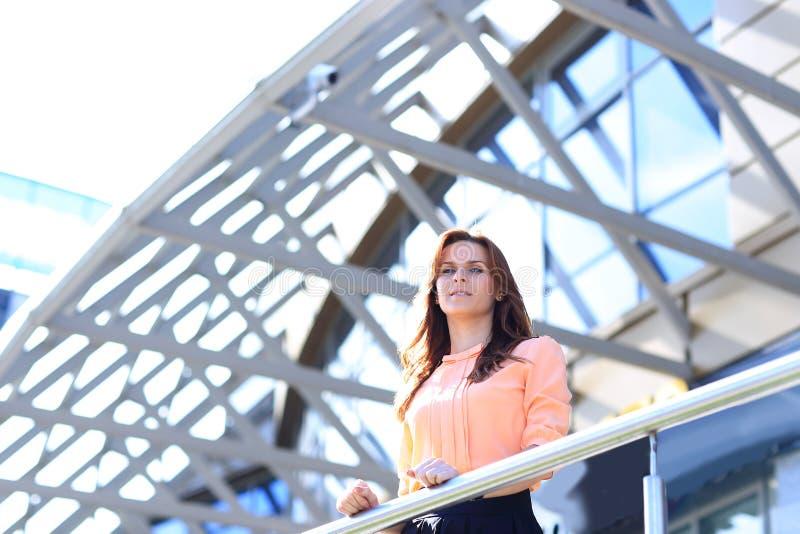 Mujer de negocios moderna que se coloca en el balcón de un edificio de oficinas moderno imágenes de archivo libres de regalías