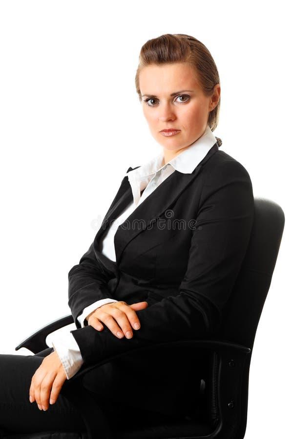 Mujer de negocios moderna seria que se sienta en silla fotografía de archivo libre de regalías