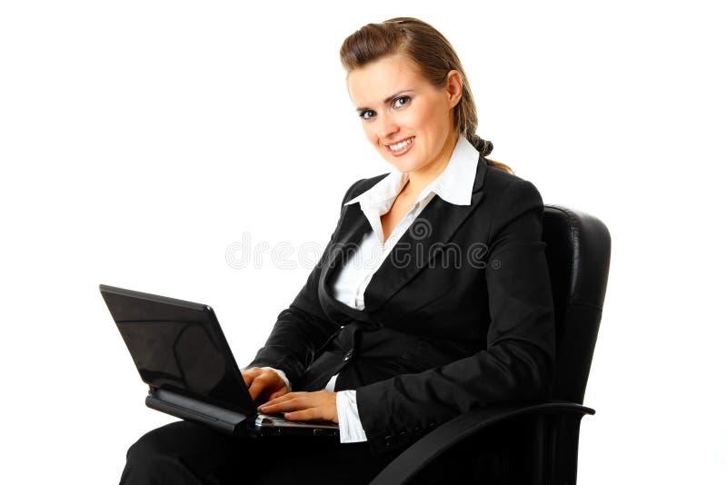 Mujer de negocios moderna sonriente que usa la computadora portátil foto de archivo libre de regalías