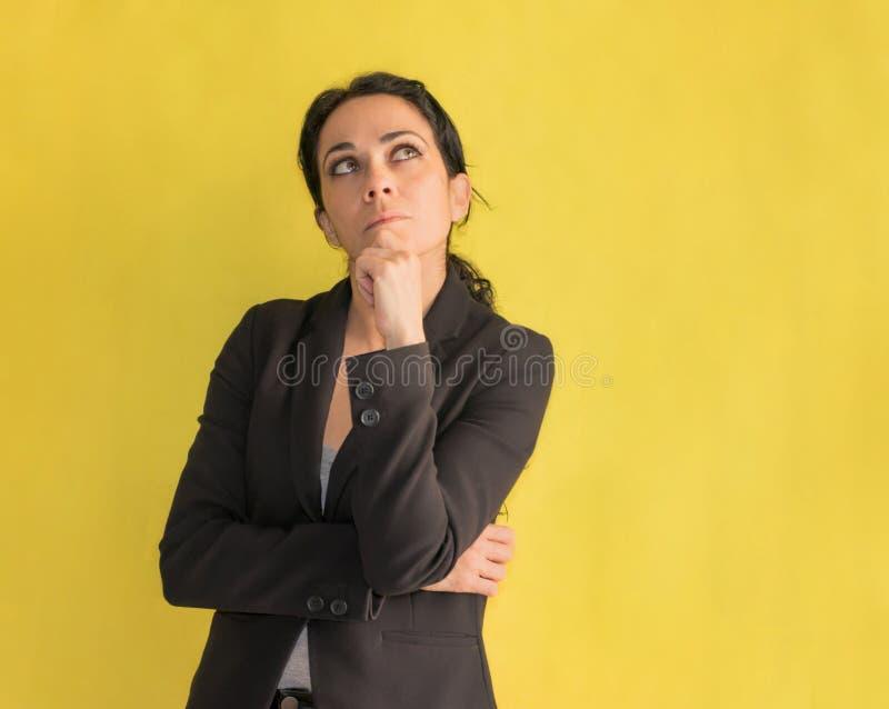 Mujer de negocios morena con la mano en la barbilla, pensando en una cierta pregunta imagenes de archivo