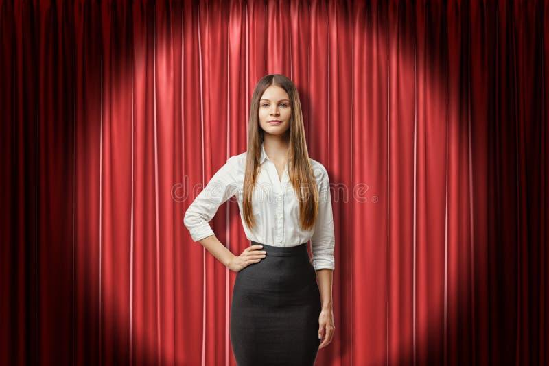 Mujer de negocios morena joven que lleva la falda negra y la camisa blanca en fondo rojo de las cortinas de la etapa imágenes de archivo libres de regalías