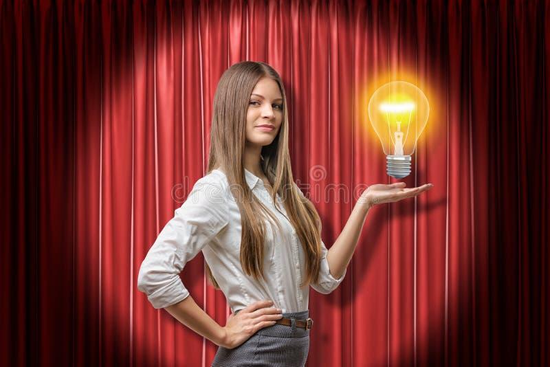 Mujer de negocios morena joven que sostiene el bulbo de ne?n de la luz ?mbar en fondo rojo de las cortinas de la etapa foto de archivo
