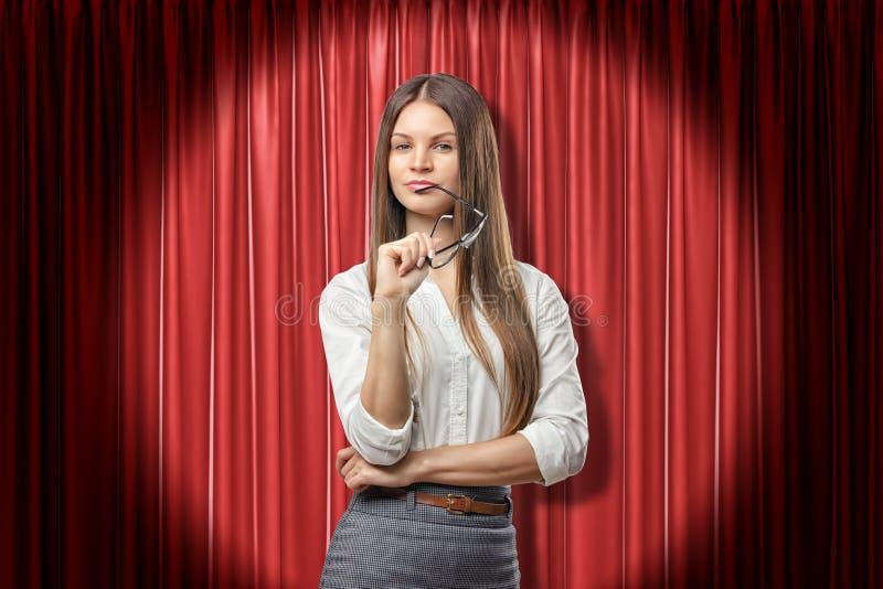 Mujer de negocios morena seria joven con los vidrios que piensa en fondo rojo de las cortinas de la etapa foto de archivo libre de regalías