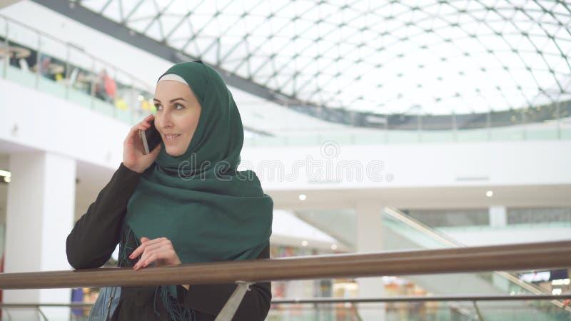 Mujer de negocios musulmán que habla en el teléfono en el centro de negocios moderno fotos de archivo libres de regalías