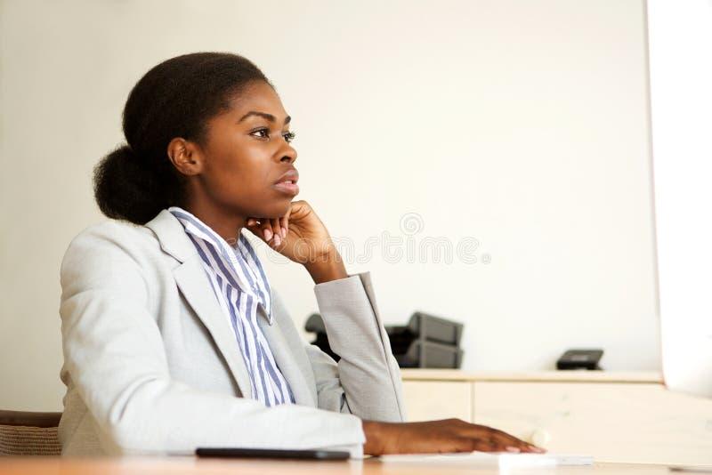 Mujer de negocios negra joven seria que se sienta en la oficina que mira la pantalla de ordenador fotos de archivo libres de regalías