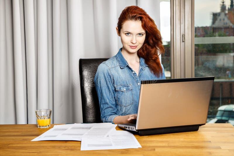Mujer de negocios o muchacha joven pelirroja del estudiante que trabaja con los documentos y el ordenador portátil cerca de venta imagen de archivo