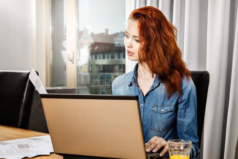 Mujer de negocios o muchacha joven pelirroja del estudiante que trabaja con los documentos y el ordenador portátil cerca de venta imagen de archivo libre de regalías